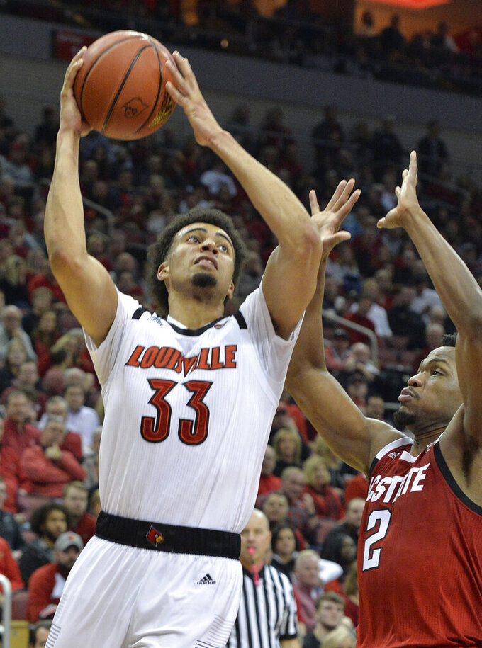 Louisville forward Jordan Nwora (33) shoots next to North Carolina State guard Torin Dorn (2) during the second half of an NCAA college basketball game in Louisville, Ky., Thursday, Jan. 24, 2019. Louisville won 84-77. (AP Photo/Timothy D. Easley)