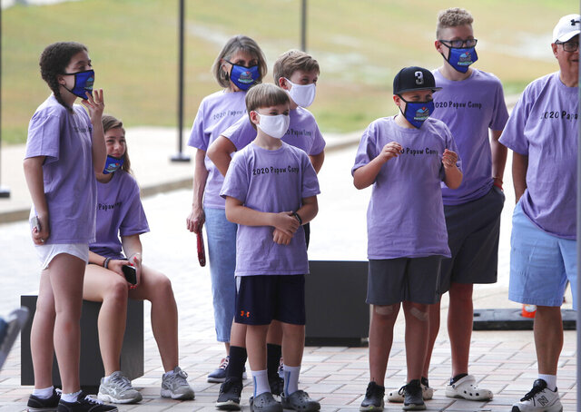 Amid concerns of the spread of COVID-19, baseball fans wear masks as they wait to tour the new Texas Rangers baseball park in Arlington, Texas, Monday, June 1, 2020. (AP Photo/LM Otero)