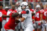 Ohio State defensive end Tyreke Smith, left, sacks Cincinnati quarterback Desmond Ridder during the first half of an NCAA college football game Saturday, Sept. 7, 2019, in Columbus, Ohio. (AP Photo/Jay LaPrete)