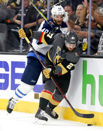 Vegas Golden Knights defenseman Shea Theodore, right, knocks the puck away from Winnipeg Jets right wing Joel Armia during the third period of Game 3 of the NHL hockey playoffs Western Conference finals Wednesday, May 16, 2018, in Las Vegas. (AP Photo/John Locher)