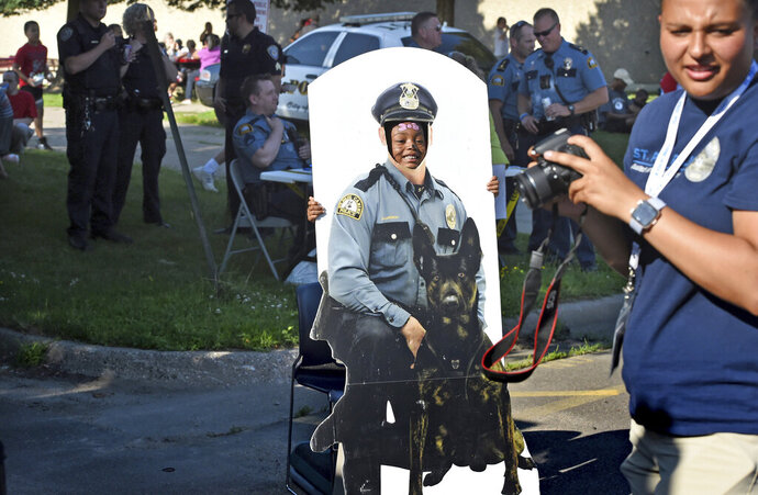 Kids get their picture taken with a cardboard cutout of a police officer and a K-9 dog during a Safe Summer Nights event at Martin Luther King Recreation Center in St. Paul, Minn. on Thursday, July 11, 2019. After a series of high-profile K-9 bites and an external audit, K-9s are now being used in St. Paul only for the most violent offenses. A new policy has the K-9s focus on tracking and tries to have officers arrest suspects, rather than a dog biting a person to get him into custody. (Jean Pieri/Pioneer Press via AP)