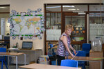 Year 6 teacher Jane Cooper uses a 2 meter length of ruler and pipe to check seat spacings in her classroom as measures are taken to prevent the transmission of coronavirus before the possible reopening of Lostock Hall Primary school in Poynton near Manchester, England, Wednesday May 20, 2020. ( AP Photo/Jon Super)