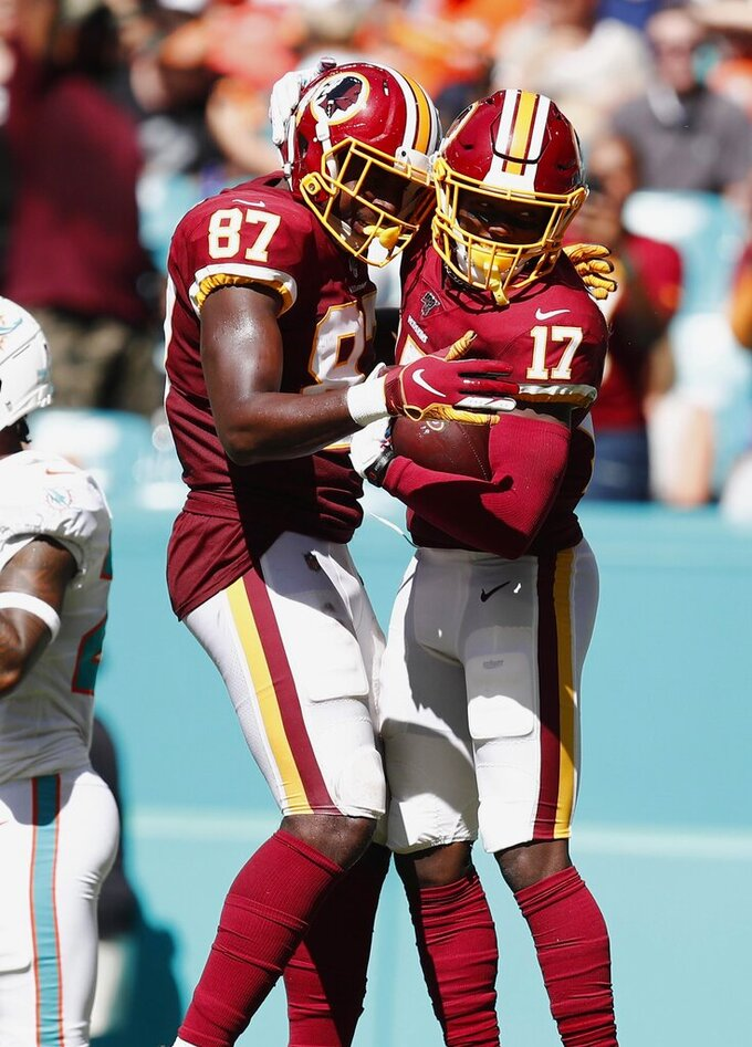 Washington Redskins tight end Jeremy Sprinkle (87) congratulates wide receiver Terry McLaurin (17) after McLaurin scored a touchdown, during the second half at an NFL football game against the Miami Dolphins, Sunday, Oct. 13, 2019, in Miami Gardens, Fla. (AP Photo/Brynn Anderson)