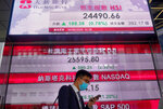 A man wearing a face mask walks past a bank's electronic board showing the Hong Kong share index at Hong Kong Stock Exchange Tuesday, June 30, 2020. Asian shares are rising, cheered by a rally on Wally Street that underlined some optimism about global business performance despite the ongoing coronavirus pandemic. (AP Photo/Vincent Yu)