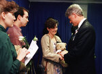 FILE - In this Sunday, April 23, 1995 file photo, Aren Almon of Oklahoma City, clutches a teddy bear as she is greeted by President Bill Clinton in Oklahoma City, Okla., after a prayer service for the victims of Wednesday's deadly car bomb attack in downtown Oklahoma City. Almon's 1-year old daughter, Baylee, was killed in the attack. The pandemic is playing out in a divided country under a president who thrives on rousing his supporters and getting a rise out of those who don't like him, whether that means forgoing a mask, playing golf while millions hunker down or thrashing opponents on Twitter.  (AP Photo/Pat Sullivan)