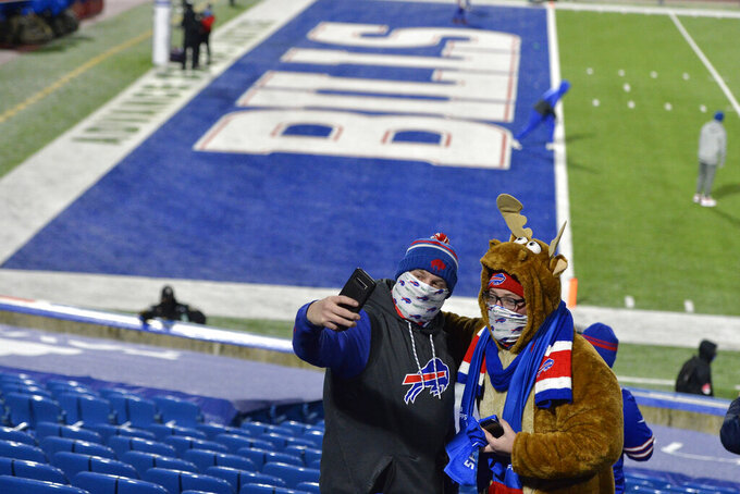 Buffalo Bills fans pose for photos at Bills Stadium before an NFL divisional round football game against the Baltimore Ravens Saturday, Jan. 16, 2021, in Orchard Park, N.Y. (AP Photo/Adrian Kraus)