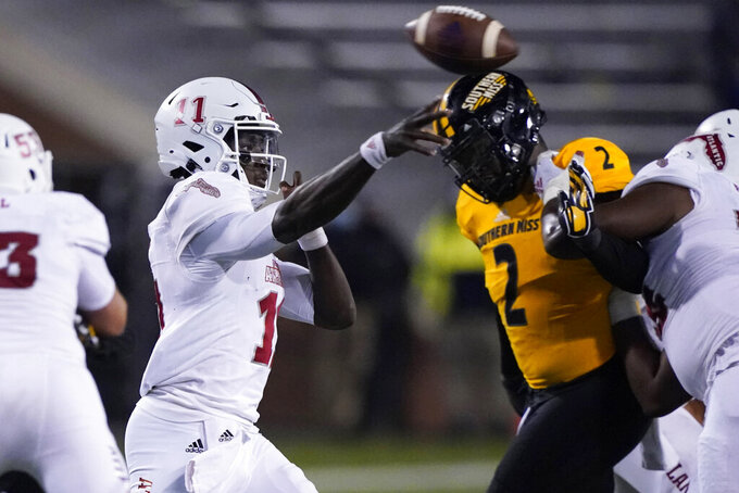 Florida Atlantic quarterback Javion Posey (11) passes while under pressure from Southern Mississippi defensive lineman Eriq Kitchen (2) during the second half of an NCAA college football game Thursday, Dec. 10, 2020, in Hattiesburg, Miss. (AP Photo/Rogelio V. Solis)