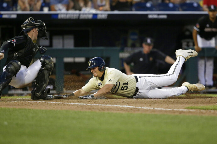 Vanderbilt's JJ Bleday (51) scores against Louisville catcher Henry Davis on a double by Ethan Paul during the ninth inning of an NCAA College World Series baseball game in Omaha, Neb., Friday, June 21, 2019. (AP Photo/Nati Harnik)
