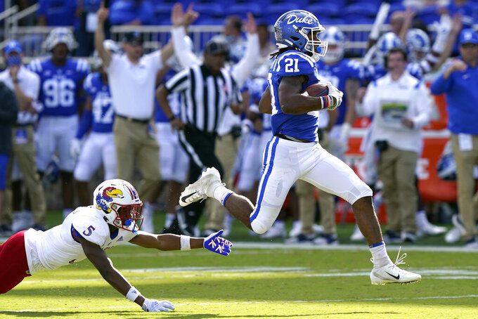 Duke running back Mataeo Durant (21) runs for a touchdown while Kansas safety O.J. Burroughs (5) misses the tackle during the first half of an NCAA college football game in Durham, N.C., Saturday, Sept. 25, 2021. (AP Photo/Gerry Broome)