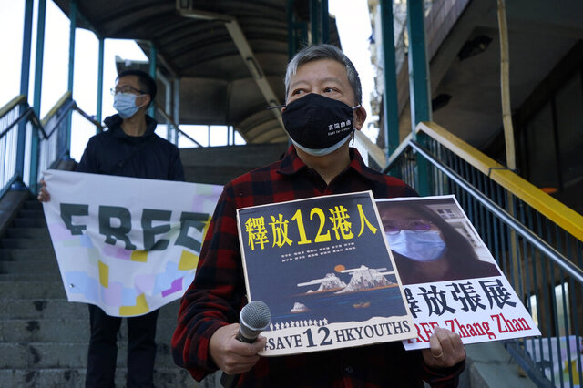 FILE - In this Dec. 28, 2020, file photo, pro-democracy activists, including Lee Cheuk-Yan, right, hold placards with the picture of journalist Zhang Zhan as they march to the Chinese central government's liaison office, in Hong Kong. Although human rights campaigners around the globe were stunned to see a raging mob storm the U.S. Capitol, they say they were heartened and inspired because the system ultimately prevailed. Facing charges of unlawful assembly for organizing a banned pro-democracy rally in Hong Kong last year, Lee worries that the rampage strengthens the hand of the Chinese territory's Communist rulers in Beijing, offering a propaganda opportunity to denigrate democracy that Chinese state-controlled media seized upon. (AP Photo/Kin Cheung, File)