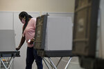 Volunteer Arsinia Dempsey cleans a voting booth between voters at the North End Senior Center, Tuesday, Aug. 11, 2020, in Hartford, Conn. (AP Photo/Jessica Hill)