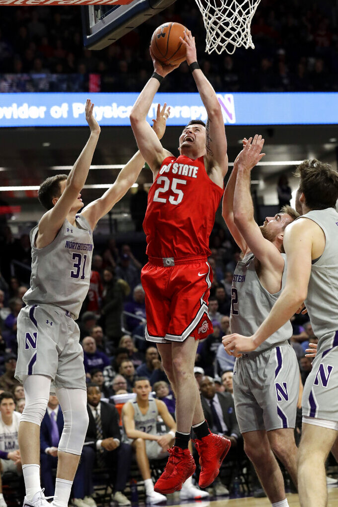 Ohio State forward Kyle Young, center, shoots against Northwestern forward Robbie Beran, left, and guard Pat Spencer during the first half of an NCAA college basketball game in Evanston, Ill., Sunday, Jan. 26, 2020. (AP Photo/Nam Y. Huh)