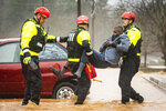 Winston-Salem Fire Department firefighters with the Rescue Task Force rescue Donald Harold from his home at Liberty Landing Apartments as flood waters rise around the building on Thursday, Feb. 6, 2020 in Winston-Salem, N.C. (Andrew Dye/The Winston-Salem Journal via AP)