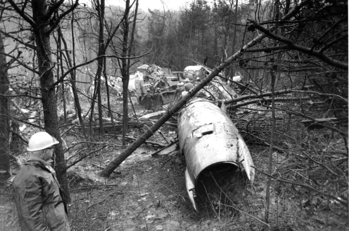 FILE - In this Nov. 15, 1970, file photo, a fireman looks over the wreckage of a DC-9 jet that was carrying 75 people including 26 members of the Marshall University football team, in Kenova, W.Va. Marshall and East Carolina will open the 2020 football season a week earlier to accommodate a national television broadcast to mark the 50th anniversary of the worst disaster in U.S. sports history.  (AP Photo/File)