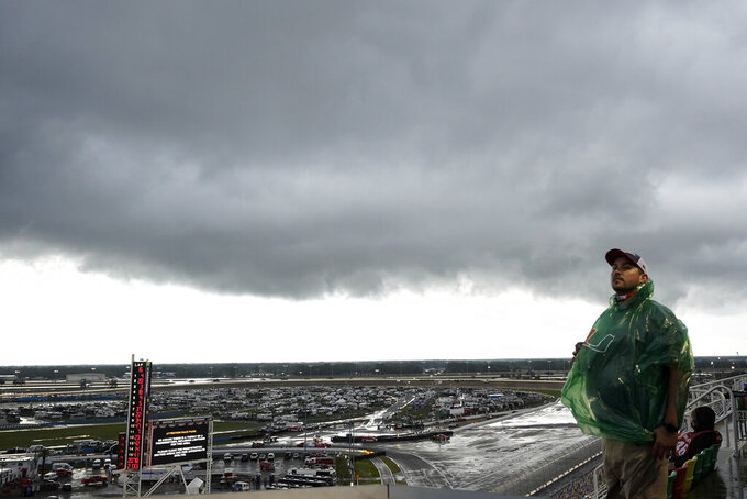 A fan waits during a weather delay in the NASCAR Daytona 500 auto race at Daytona International Speedway, Sunday, Feb. 14, 2021, in Daytona Beach, Fla. (AP Photo/Chris O'Meara)
