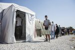 FILE - Migrants wait in a queue to do tests for the new coronavirus in Moria refugee camp on the northeastern Aegean island of Lesbos, Greece, on Friday, Sept. 4, 2020. A major testing and contact-tracing operation at Greece's largest migrant camp on the eastern island of Lesbos has so far detected 17 confirmed cases of COVID-19 infection among the 12,500 people living in the overcrowded facility, officials said on Tuesday, Sept. 8, 2020. (AP Photo/Panagiotis Balaskas, File)