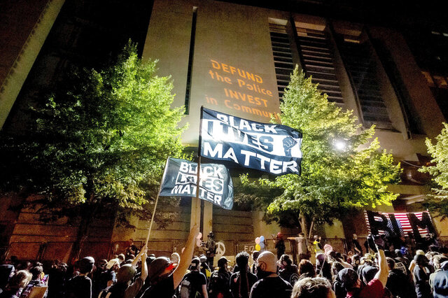 FILE - In this July 31, 2020 file photo, Black Lives Matter protesters gather at the Mark O. Hatfield United States Courthouse in Portland, Ore. At least two federal buildings in Portland have been closed and the FBI is investigating after a threat of violence was reported, the officials said Friday, Aug. 21, 2020. Investigators are trying to determine whether the threat is credible, the FBI said in a statement. The Mark O. Hatfield Federal courthouse, which was the site of weeks of violent protests last month, was closed, as was the Portland office of the U.S. Bankruptcy Court. (AP Photo/Noah Berger, File)