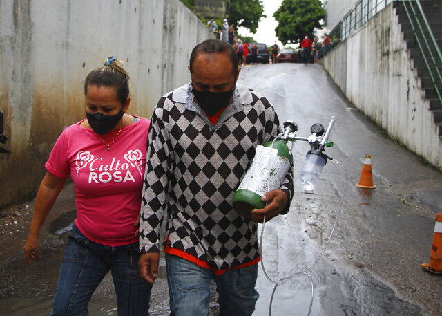Accompanied by his wife, Rafael Pereira carries an oxygen tank that bought for his mother in law, who is hospitalized with COVID-19, amid the new coronavirus pandemic at the at the 28 Agosto Hospital, in Manaus, Brazil, Thursday, Jan 14, 2021. Scores of COVID-19 patients in the Amazon rainforest's biggest city will be transferred out of state as the local health system collapses and dwindling stocks of oxygen tanks begin to falter. (AP Photos/Edmar Barros)