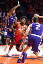 Illinois guard Andres Feliz (10) drives to the basket between Northwestern forward Vic Law (4) and guard Ryan Greer (2) during the first half of an NCAA college basketball game in Champaign, Ill., Sunday, March 3, 2019. (AP Photo/Stephen Haas)