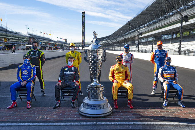 Past winners of the Indianapolis 500 pose with the Borg-Warner Trophy on the start/finish line at Indianapolis Motor Speedway in Indianapolis, Friday, Aug. 21, 2020. They are left to right, front row, Alexander Rossi, Will Power, of Australia, Ryan Hunter-Reay, and Takuma Sato, of Japan. Back row, left to right, Simon Pagenaud, of France, Helio Castroneves, of Brazil, Tony Kanaan, of Brazil, and Scott Dixon, of New Zealand. The 104th running of the Indianapolis 500 auto race is scheduled to run on Sunday.(AP Photo/Michael Conroy)