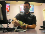 An employee counts cash in the sports book at Freehold Raceway in Freehold, N.J. on Oct. 24, 2020. Freehold has become the third New Jersey horse track to offer sports betting, and it joins eight Atlantic City casinos in doing so. (AP Photo/Wayne Parry)