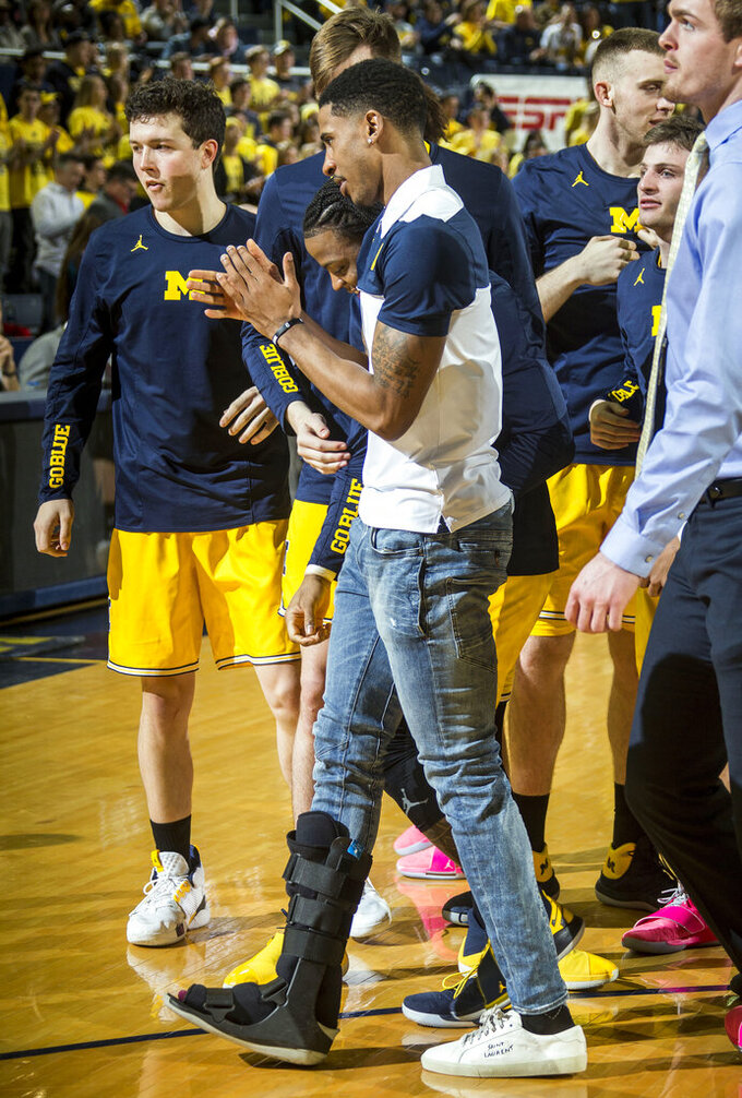 Michigan guard Charles Matthews, center, walks with a right foot cast, before an NCAA college basketball game against Nebraska at Crisler Center in Ann Arbor, Mich., Thursday, Feb. 28, 2019. Matthews injured his right foot during Michigan's loss to Michigan State last Sunday. (AP Photo/Tony Ding)
