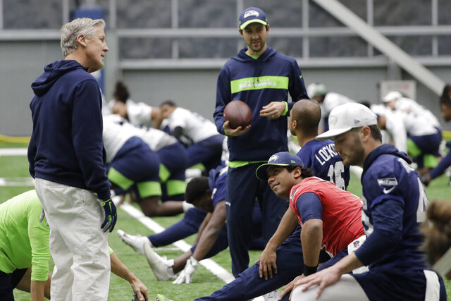 Seattle Seahawks head coach Pete Carroll, left, talks with quarterback Russell Wilson, second from right, during warmups before NFL football practice, Friday, Dec. 27, 2019, in Renton, Wash. (AP Photo/Ted S. Warren)