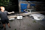 A resident points to a car smashed by a fallen electricity pole in the aftermath of a blast at a nearby gas plant in Yima city central China's Henan province during the early hours of Saturday, July 20, 2019. The Friday evening explosion shattered windows 3 kilometers (1.9 miles) away, and knocked off doors inside buildings, killing some and injuring others. (Chinatopix via AP) CHINA OUT