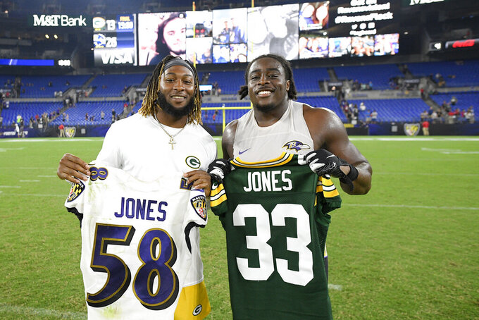 Twin brothers Green Bay Packers running back Aaron Jones, left, and Baltimore Ravens linebacker Alvin Jones pose for a photo after exchanging jerseys after an NFL football preseason game, Thursday, Aug. 15, 2019, in Baltimore. The Ravens won 26-13. (AP Photo/Nick Wass)