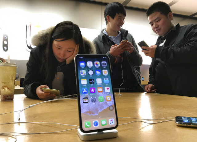 FILE - In this Monday, Nov. 6, 2017, file photo, shoppers check out smart phones at a store  in Beijing, China. Companies including the Chinese arm of TripAdvisor Inc. have been ordered by regulators to overhaul their mobile phone apps in what the Chinese government says is a crackdown on pornography and other improper content. (AP Photo/Ng Han Guan, File)