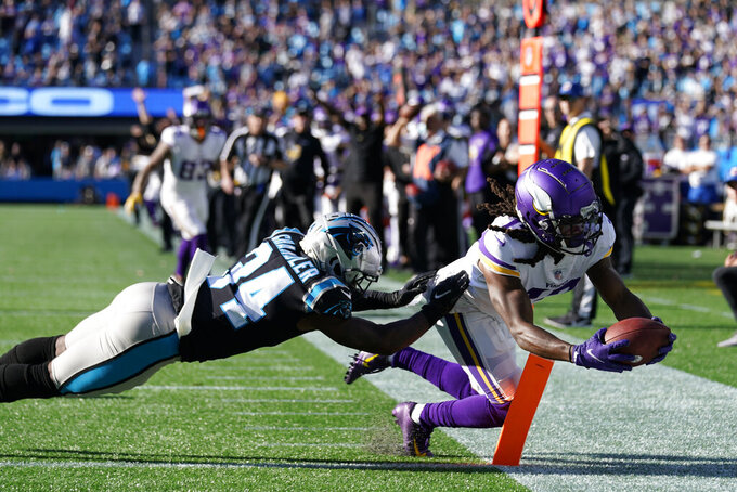 Minnesota Vikings wide receiver K.J. Osborn (17) makes the game-winning catch against Carolina Panthers safety Sean Chandler (34) during overtime of an NFL football game, Sunday, Oct. 17, 2021, in Charlotte, N.C. The Minnesota Vikings won 34-28. (AP Photo/Gerald Herbert)