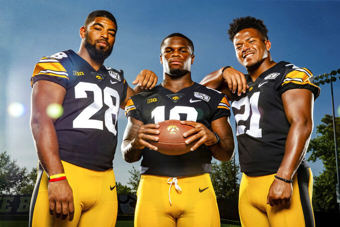 Iowa running backs Toren Young, from left, Mekhi Sargent and Ivory Kelly-Martin pose for a photo during the team's NCAA college football media day, Friday, Aug. 9, 2019, in Iowa City, Iowa. (Zach Boyden-Holmes/The Des Moines Register via AP)
