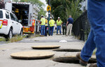 FILE-- In this Sept. 14, 2018 file photo, a worker with Columbia gas stands over an open manhole as the crew works to make sure there are no gas leaks at the corner of Parker and Salem Streets in Lawrence, Mass. The series of natural gas explosions and fires in Massachusetts last September has cost provider Columbia Gas of Massachusetts more than $1 billion. (AP Photo/(AP Photo/Mary Schwalm, File)