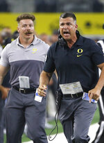 Oregon coach Mario Cristobal runs down the sideline as Oregon plays Auburn during the first half of an NCAA college football game Saturday, Aug. 31, 2019, in Arlington, Texas. Auburn won 27-21. (AP Photo/Ron Jenkins)