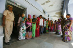 Indians stands in queue to cast their vote for general election in Ahmadabad, India, Tuesday, April 23, 2019. Indians are voting Tuesday in the third phase of the general elections with campaigning by Prime Minister Narendra Modi's Hindu nationalist party and the opposition marred by bitter accusations and acrimony. The voting over seven phases ends May 19, with counting scheduled for May 23. (AP Photo/Ajit Solanki)
