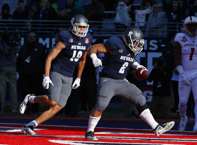 Nevada running back Devonte Lee (2) celebrates with Reese Neville in the second half after scoring a touchdown during an NCAA college football bowl game, Saturday, Dec. 29, 2018, in Tucson, Ariz. AP Photo/Rick Scuteri)
