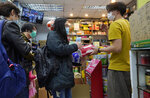 People wearing face masks queue up to purchase tissue papers at a pharmacy in Hong Kong, Thursday, Feb. 6, 2020. Ten more people were sickened with a new virus aboard one of two quarantined cruise ships with some 5,400 passengers and crew aboard, health officials in Japan said Thursday, as China reported 73 more deaths and announced that the first group of patients were expected to start taking a new antiviral drug. (AP Photo/Vincent Yu)