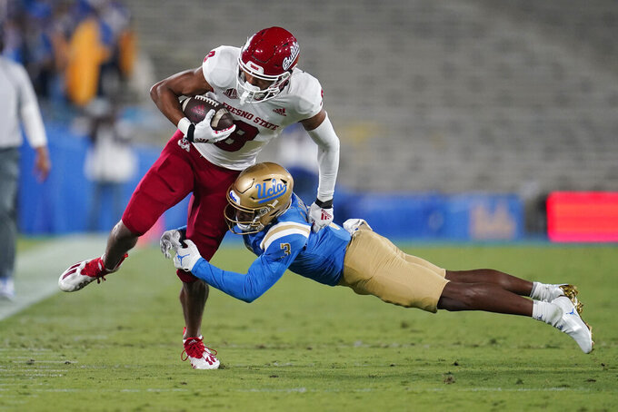 Fresno State wide receiver Ty Jones (8) is tackled by UCLA defensive back Cameron Johnson (3) during the first half of an NCAA college football game Saturday, Sept. 18, 2021, in Pasadena, Calif. (AP Photo/Marcio Jose Sanchez)