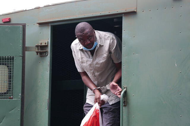 Zimbabwe investigative journalist Hopewell Chin'ono gets out of a prison van at the magistrates courts in handcuffs in Harare, Friday, Nov. 6, 2020. Chin'ono is one of Zimbabwe's most prominent critics of President Emmerson Mnangagwa's administration, accusing it of corruption and human rights abuses. The government denies the charges. (AP Photo/Tsvangirayi Mukwazhi)