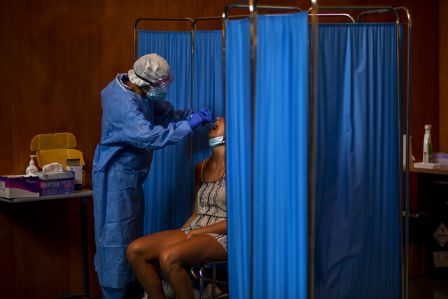 A Spanish NGO Open Arms volunteer takes a swab to test a woman for COVID-19, at Vilafranca del Penedes in the Barcelona province, Spain, Tuesday, Aug. 11, 2020. Spain is facing another surge in coronavirus infections not even two months after beating back the first wave. (AP Photo/Emilio Morenatti)