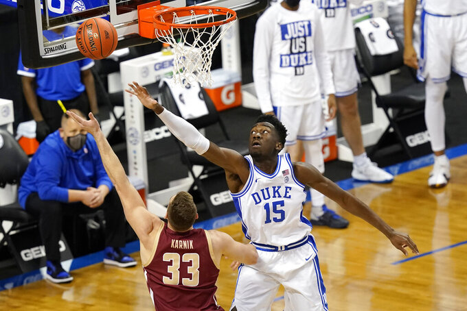 Duke center Mark Williams (15) tries top block the shot of Boston forward James Karnik (33) during the first half an NCAA college basketball game in the first round of the Atlantic Coast Conference tournament in Greensboro, N.C., Tuesday, March 9, 2021. (AP Photo/Gerry Broome)