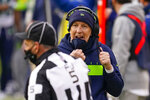 Seattle Seahawks head coach Pete Carroll lowers his face mask to talk to official Jim Quirk (5) during the second half of an NFL football game against the Washington Football Team, Sunday, Dec. 20, 2020, in Landover, Md. (AP Photo/Andrew Harnik)