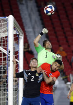 Chile goalkeeper Claudio Bravo, top, clears the ball on a corner kick over Argentina's Lucas Martinez, left, and Chile's Paulo Diaz during the first half of an international friendly soccer match Thursday, Sept. 5, 2019, in Los Angeles. (AP Photo/Marcio Jose Sanchez)