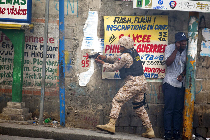 In this Monday, Nov. 18, 2019 photo, a police officer points his gun at residents of Delmas 95 district during a protest to demanding the resignation of Haiti's president Jovenel Moise in Port-au-Prince, Haiti. At least four people were shot and wounded during a small protest in Haiti's capital after a speech by embattled President Jovenel Moise. A local journalist, a police officer and two protesters were rushed away with apparent bullet wounds. (AP Photo/Dieu Nalio Chery)