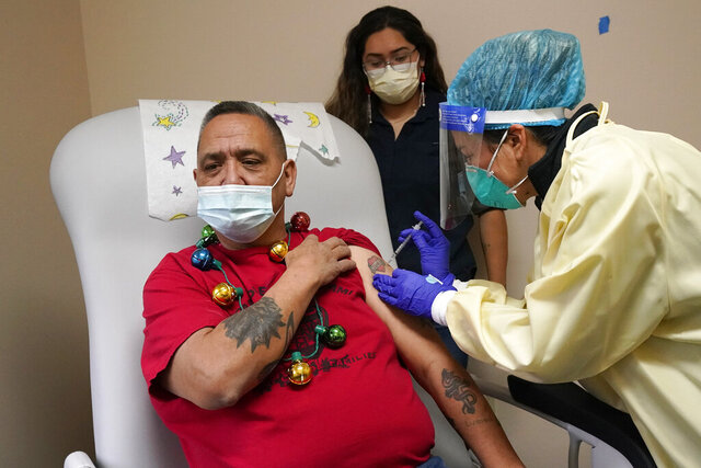 Lummi Nation member James Scott (native name Qwelexwbed), left, receives the first COVID-19 vaccination on the Lummi Reservation by registered nurse Alyssa Lane, Thursday, Dec. 17, 2020, near Bellingham, Wash. Scott's granddaughter, Mackayla Alvarez, the family's oral historian, looks on to witness the moment. The Native American tribe began rationing its first 300 doses of vaccine as it fights surging cases with a shelter-in-place order. (AP Photo/Elaine Thompson)