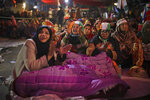 In this Wednesday, Jan. 22, 2020 photo, women protesters share a quilt as they listen to a speaker inside a tent at the protest site in New Delhi's Shaheen Bagh area, India. The gathering at Shaheen Bagh started with a handful of women appalled by the violence at a nearby Muslim university during protests against the law on Dec. 15. Since then it has slowly morphed into a nationwide movement, with many women across the country staging their own sit-ins. They sing songs of protest and chant anti-government slogans, some cradling babies, others laying down rugs to make space for more people to sit. (AP Photo/Altaf Qadri)