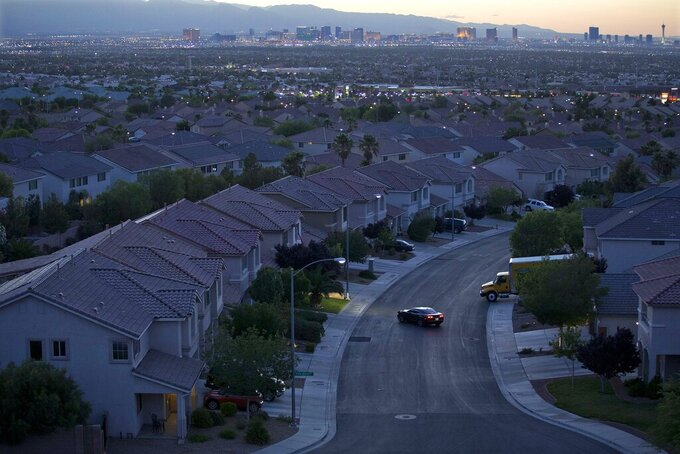 FILE- In this Wednesday, May 29, 2013, photo, the Las Vegas skyline glows at dusk as a motorist pulls into the driveway of a home, in Henderson, Nev. Home prices in the Las Vegas area are setting monthly records, according to an industry survey putting the median price of existing single-family houses at $375,000 in April. A report released Thursday, May 6, 2021, by the organization Las Vegas Realtors said local home prices have never been higher and the housing supply has rarely, if ever, been tighter. (AP Photo/Julie Jacobson, File)