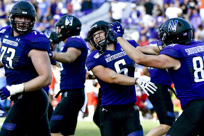 Northwestern running back Drake Anderson, center, celebrates with Northwestern offensive lineman Gunnar Vogel (73) and wide receiver Bennett Skowronek (88) after Anderson scored a touchdown against UNLV during the second half of an NCAA college football game, Saturday, Sept. 14, 2019, in Evanston, Ill. (AP Photo/Matt Marton)