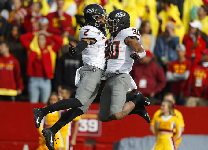 Oklahoma State wide receiver Tylan Wallace, left, celebrates his touchdown with Oklahoma State running back Chuba Hubbard, right, during the first half of an NCAA college football game against Iowa State, Saturday, Oct. 26, 2019, in Ames, Iowa. (AP Photo/Matthew Putney)