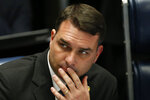 Brazilian Senator Flavio Bolsonaro, son of the nation's president, attends the final voting session on pension reform at the Senate in Brasilia, Brazil, Tuesday, Oct. 22, 2019. The most meaningful impact of the reform is the establishment of a minimum age for retirement at 65 for men and 62 for women. (AP Photo/Eraldo Peres)